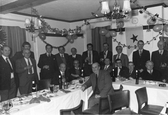 black and white photograph of men eating christmas dinner