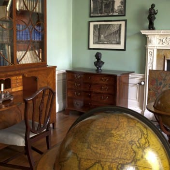 The study in the Georgian House Museum featuring two fall standing globes, a French dresser and a fireplace.
