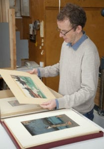 Paper Conservator Harry Metcalf inspects a box of the prints