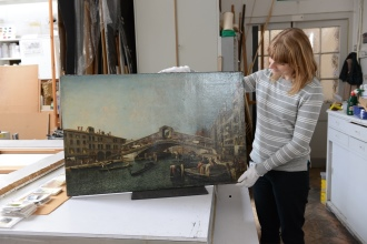 Photo of a conservator holding the rialto bridge painting