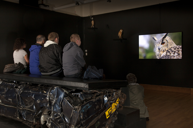 Photo of people watching a video at Jeremy Deller's English Magic exhibition at Bristol Museum & Art Gallery