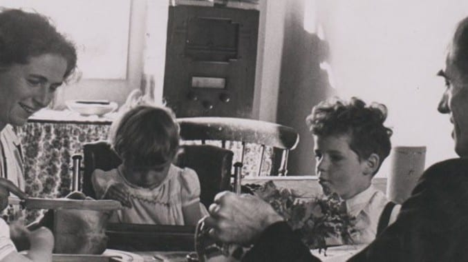 black and white photograph of a family sitting round a table eating