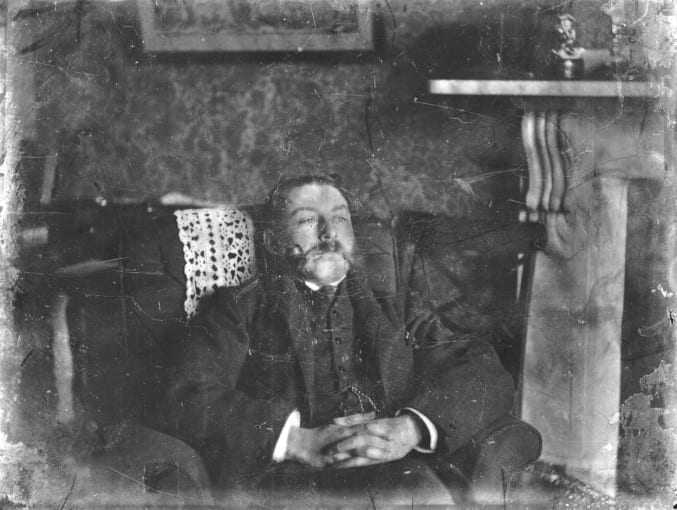 photograph of a chap with an extravagant moustache relaxing in his living room