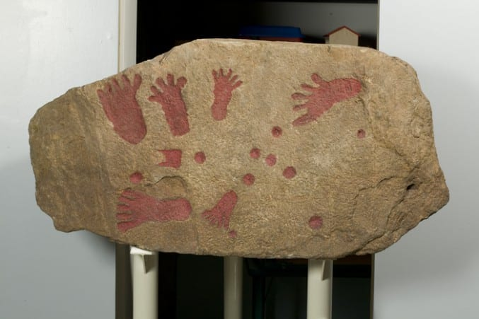 Image of a slab of rock with red footprints and handprints on it