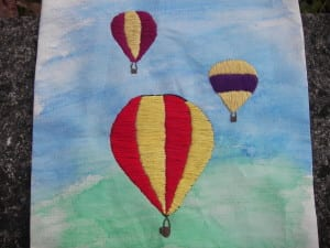 Three hot air balloons embroidered on a flag