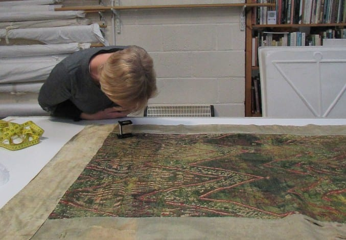 Photo of a conservator assessing textiles