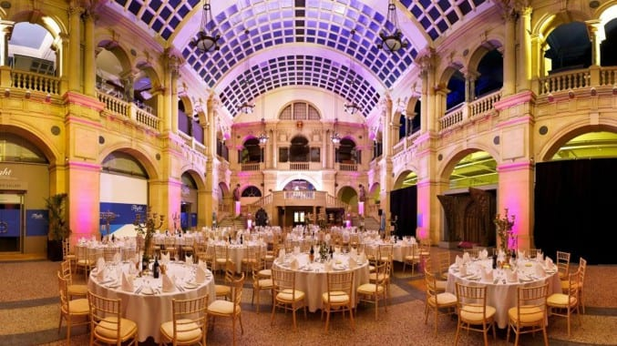 Photo of the rear hall in Bristol Museum & Art Gallery at night, with tables set up for an evening event
