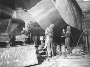 Black and white photograph of three people spray painting the underside of a boat