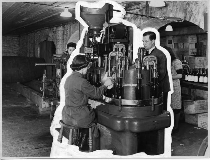 Black and white photograph of a seated woman and standing man working a machine in a basement
