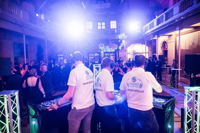 Three DJs and a crowd of people in the front hall of Bristol Museum at a silent disco
