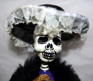 Photo of a doll with a skull face and lace hat