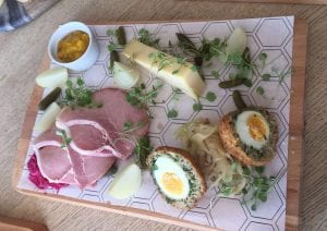 A wooden chopping board with M Cafe's sharing platter on top featuring ham, scotch eggs, cheese and pickles