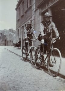 Two children riding bicycles in the street outside the Guild of the Brave Poor Things