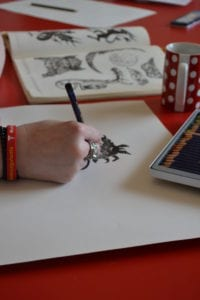 Close up of a person drawing a print of a mythical creature. Their hand and the drawing is in view, accompanied by sketchbooks and coloured artist pencils.
