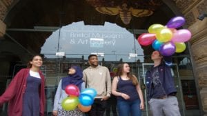 Group of young people stand outside the museum smiling and holding balloons.