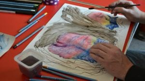 An image of someone painting a colourful design at the shine project