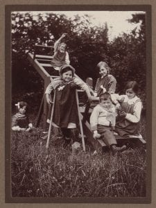 Children sat on a see-saw in the countryside
