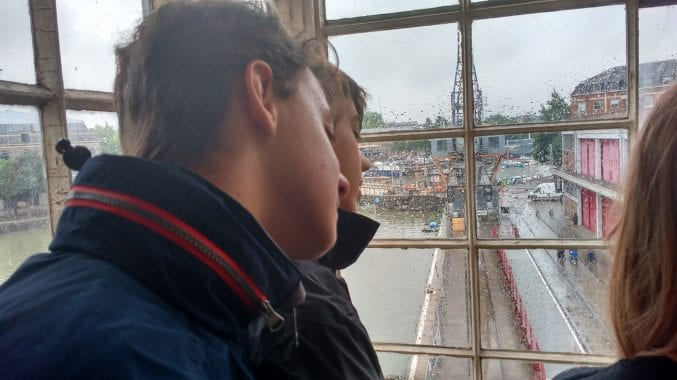 Two people stood in the cabin of an electric crane looking over the harbour below