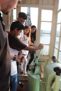 Four young people in a crane cabin learning how to control it