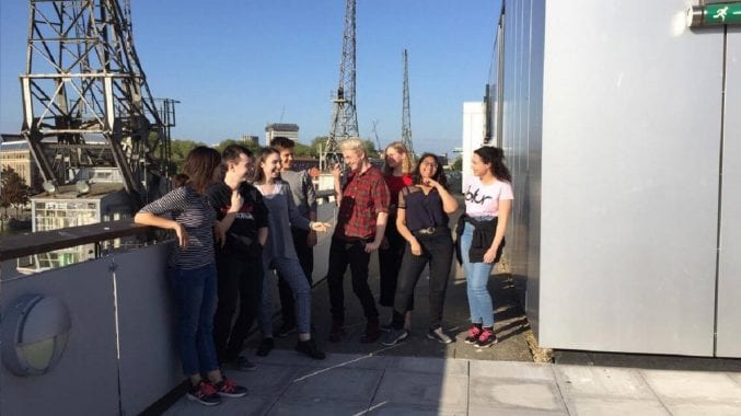 A group of seven young people stood on M Shed's terrace with Claire Simmons - the engagement officer for young people