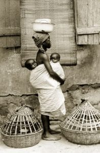 Photograph of a Yoruba woman with two babies in her arms and carrying baskets on her head