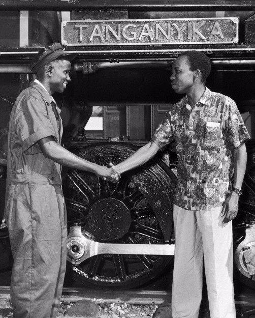Black and white image showing Dr Julius Nyerere, first President of an independent Tanzania, greeting a train driver.