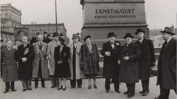 A group of people stood beside the Ernst August monument in Hannover