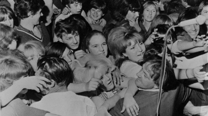 A black and white image of a crowd of people at a music show in Filwood in 1964