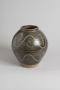 'Ibex' pot by Bernard Leach. A brown pot with wave decoration.