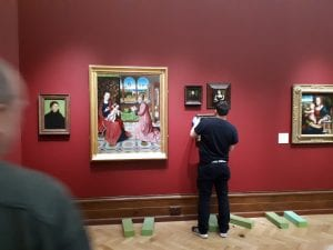 A technician in the process of hanging a painting next to the Bouts