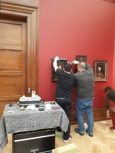 Two technicians work on hanging other paintings in the gallery. One of them holds the painting while the other uses a drill to attach it to the wall.