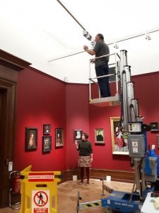 A man stood on a cherry picker working on the lighting in the gallery.