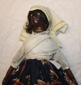 A close up of one of the dolls. There's white cloth wrapped around the head with a gold hem, a gold necklace, a white cloth top and a dark blue floral skirt.