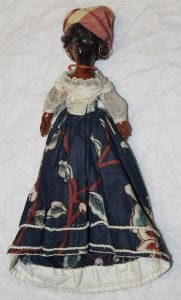 A picture showing the whole entirety of one of the dolls. There's red and white cloth wrapped around the head, a red necklace, a white cloth top and a dark blue floral skirt.