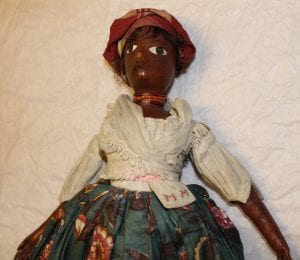 A close up of one of the dolls. There's red cloth wrapped around the head , a white cloth top, a red necklace and a blue floral skirt. 'MM' is also embroidered on the pocket