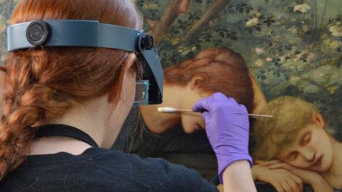 photo of a conservator cleaning a painting