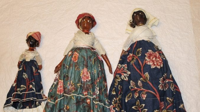 Three dolls in a line, gradually getting bigger. They all have a white cloth top and floral patterned skirts. All made by a freed (manumitted) woman in Grenada.