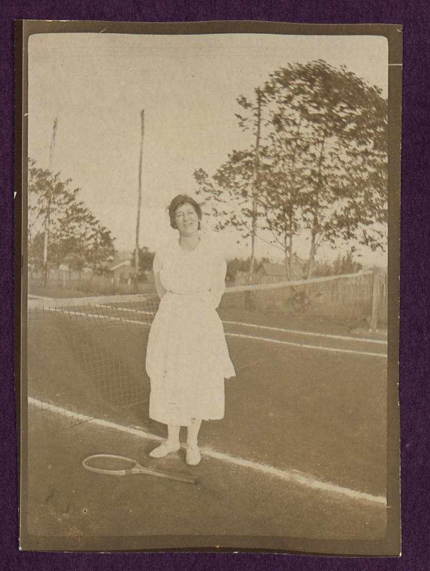 Old photograph of Maud Harpham, one of the women mentioned in the diary. She's stood on a tennis court with her racket lead on the ground.