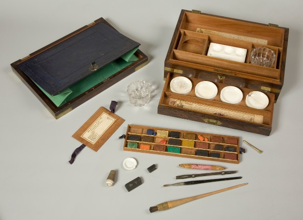 An artist's watercolour box, made of wood with brass inlays, containing various tools and materials