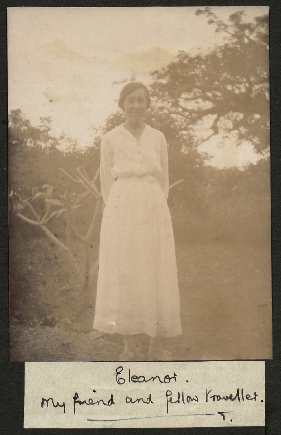 Old Photgraph of Eleanor Kemp, a woman mentioned in the diary. She is smiling, clothed in a long white dress and surrounded by trees,