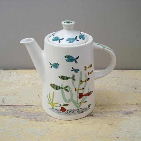 a white teapot decorated in a colourful fish design