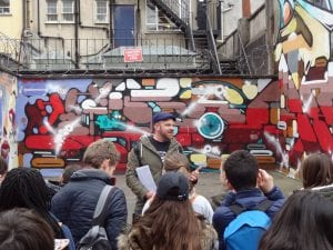 Rob Wheeler stood in front of a graffitied wall explaining it's significance to a group of walkers