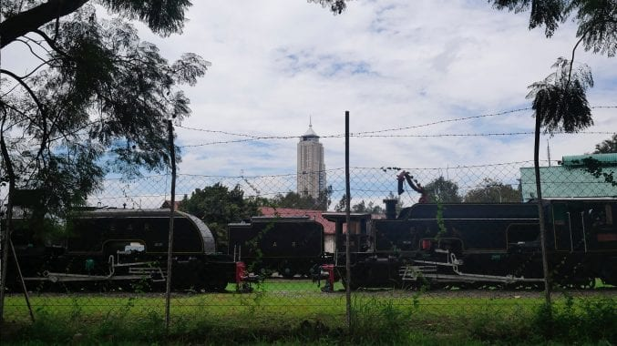 Trains at the Nairobi Railway Museum with the skyline behind.