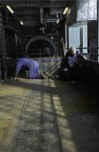 Two men in overalls on their hands and knees working on a steam train at M Shed