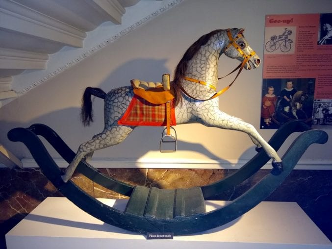 Photo of the rocking horse on display under a staircase at blaise castle house museum