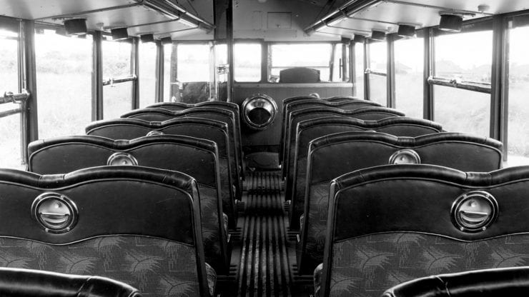 black and white photo of the inside of a 1960s bus