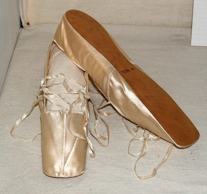 Photo of a pair of cream satin ballet shoes