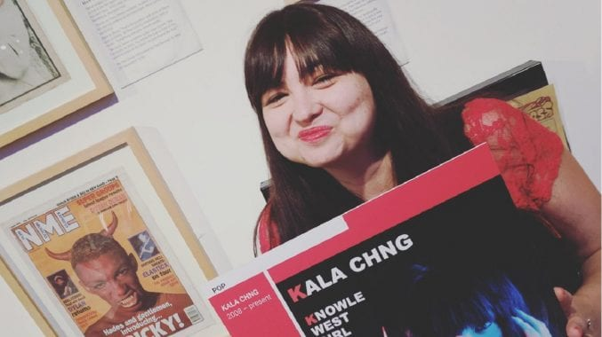 KALA CHNG holding her EP in the Bristol Music exhibition at M Shed