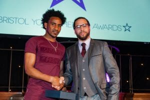 Mulue being presented with the 'Arts & Culture Hero' award by music producer Roni Size at the Bristol Young Heroes Awards