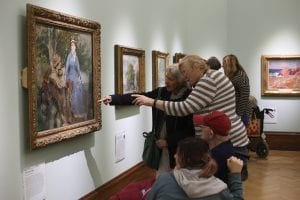A picture taken from a Dementia friendly creative cafe - a group of people looking at a painting in the French gallery